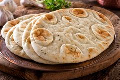 Garlic Cilantro Naan Bread. Fresh garlic cilantro naan bread on a copper plate with rustic wood background stock photo