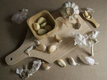 Fresh Garlic Cloves and Garlic Bulb on chopping board royalty free stock photos