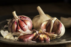 Fresh garlic cloves in moody natural lighting set up with vintag Stock Images