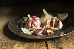 Fresh garlic cloves in moody natural lighting set up with vintag Stock Photos