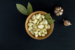 Fresh garlic heads, cloves set on a black stone surface, top view. Copy space, free space for text stock photography