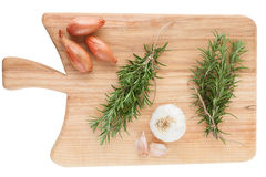Fresh garlic, onions and rosemary on cutting board Stock Images