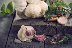 Fresh garlic, spices and salad leaves on table Stock Images