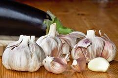 Fresh garlic on wood. Fresh garlic with egg plant on wooden background Stock Images