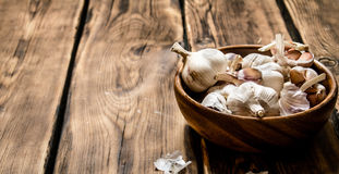 The fresh garlic in a wooden bowl. On wooden background Royalty Free Stock Photography
