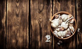 The fresh garlic in a wooden bowl. On wooden background Stock Photography