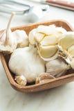 Fresh garlic in wooden bowl. Fresh garlic in wooden bowl on kitchen table Stock Image