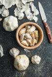 Fresh garlic in wooden bowl. Fresh garlic in wooden bowl with knife. Top view Royalty Free Stock Photography