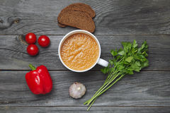 Fresh gazpacho in a bowl. And bread, parsley, pepper, garlic. Top view Stock Photography