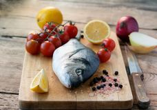 Fresh gilt-head bream fish on cutting board. With lemon, onion and tomato Stock Photos