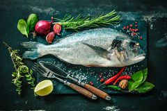 Fresh Gilt-head bream with spices and seasoning. On slate plate Stock Photography
