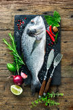 Fresh Gilt-head bream with spices and seasoning. On slate plate Stock Photo