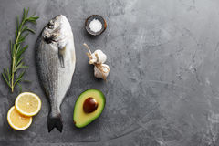 Fresh gilthead bream or dorado cooking. Fresh dorado or gilthead bream cooking with rosemary, avocado, garlic, lemon and salt on stone background Royalty Free Stock Photography