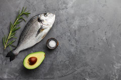 Fresh gilthead bream or dorado cooking. Fresh dorado or gilthead bream cooking with rosemary, avocado, garlic and salt on stone background Stock Photo