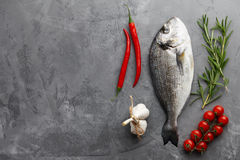 Fresh gilthead bream or dorado cooking. Fresh dorado or gilthead bream cooking with rosemary, cherry tomatoes, chili pepper and garlic on stone background Royalty Free Stock Photo