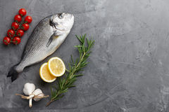 Fresh gilthead bream or dorado cooking. Fresh dorado or gilthead bream cooking with rosemary, cherry tomatoes, garlic and lemon on stone background Royalty Free Stock Images