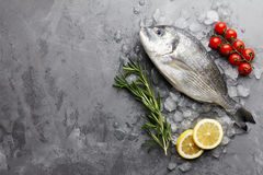 Fresh gilthead bream or dorado cooking. Fresh dorado or gilthead bream cooking with rosemary, cherry tomatoes and lemon on stone background Stock Photo