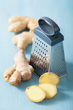 Fresh ginger and grater over blue Royalty Free Stock Photography