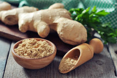 Fresh ginger root. And ground ginger spice on wooden background Stock Photography