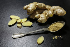 Fresh ginger root and spoon with powder on black background Stock Images