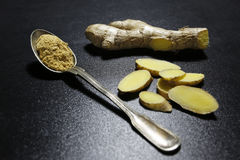 Fresh ginger root and spoon with powder on black background Stock Image