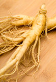 Fresh Ginseng on the wooden background Stock Photo