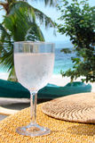 Fresh glass of water on a table, tropical beach Stock Photos