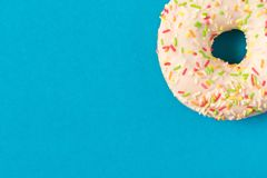 Fresh glazed donut with colorful sprinkles on a blue background.  stock images
