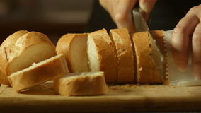 Fresh golden brown bread cutting up in kitchen on bread board. This footage is of fresh bread food being prepared and cut up with a knife on a bread board in a stock video footage