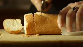 Fresh golden brown bread food prep cutting up in kitchen. This footage is of fresh bread food being prepared and cut up with a knife on a bread board in a stock video
