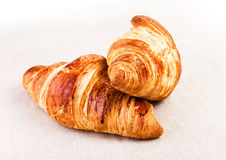 Fresh Golden Croissants on a white linen napkin on beige tablecl Royalty Free Stock Images