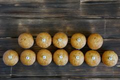 Fresh golden cupcakes with letters lie on a wooden rustic table made of pine boards. Bon appetite royalty free stock photos