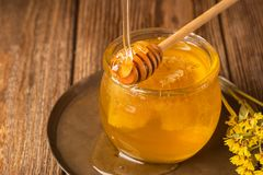 Fresh golden honey flows from a wooden spoon into a jar. Bee aromatic honey on a wooden background on the table. The concept of natural products. Horizontal royalty free stock photography