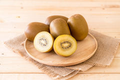 Fresh golden kiwi. In wood plate stock photos
