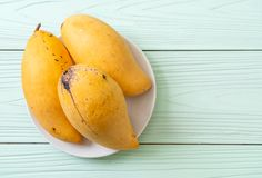 Fresh and golden mangoes. On wood background royalty free stock photos