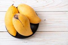 Fresh and golden mangoes. On wood background stock image