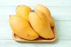 Fresh and golden mangoes. On wood background stock photos
