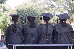 Fresh graduates. Fresh graduate girls sitting on a bench Stock Photo