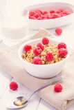 Fresh granola breakfast with raspberries and honey. On white rustic table Stock Photo