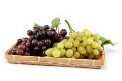 Fresh grape fruits with green leaves isolated. Stock Photography