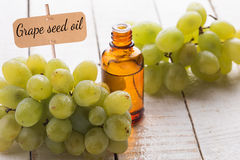 Fresh grape and grape seed oil in bottle. On white wooden background. Selective focus. Bio/organic/eco products royalty free stock images