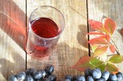 Fresh Grape juice by some Grape vines. brush of black grape juice fresh organic on wooden surface, copy space. top view. Fresh Grape juice by some Grape vines royalty free stock photo