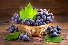 Fresh grape with leaves in a basket. On wooden background stock photo