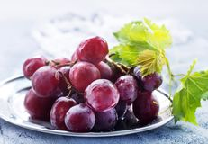 Fresh grape. On plate and on a table royalty free stock photo