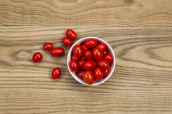 Fresh Grape Tomatoes in Bowl on Aged Wood Stock Photo