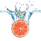 Fresh grapefruit dropped into water Royalty Free Stock Images