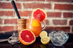 Fresh grapefruit lemonade with lime and lemons in a jug. At restaurant Stock Photography