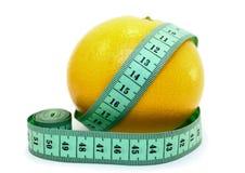 Fresh grapefruit with measuring tape. On white background closeup Royalty Free Stock Photo