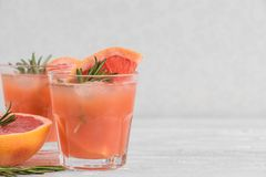 Fresh grapefruit summer alcohol cocktails in glasses, ice and rosemary on white background