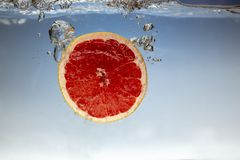 Fresh grapefruit with water splash on blue background close up. Fresh grapefruit with water splash on blue background royalty free stock photography